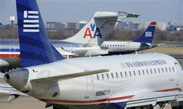 An American Airlines plane (C) is seen between two US Airways Express planes at the Ronald Reagan Washington National Airport in Arlington County, Virginia, February 10, 2013, as negotiations continue this week between parent companies US Airways Group Inc and AMR Corp on a possible $11 billion merger, creating what would be the world's largest airline. REUTERS/Mike Theiler (UNITED STATES - Tags: TRANSPORT BUSINESS)