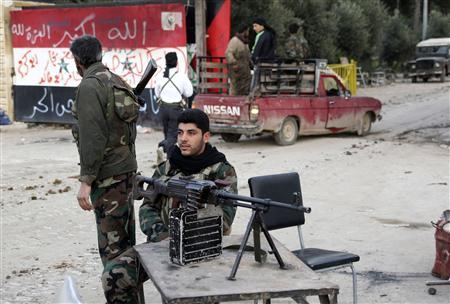 Members of the Free Syrian Army stand on a checkpoint beside the Al-Moshat school wall in Aleppo, February 10, 2013. REUTERS/Muzaffar Salman