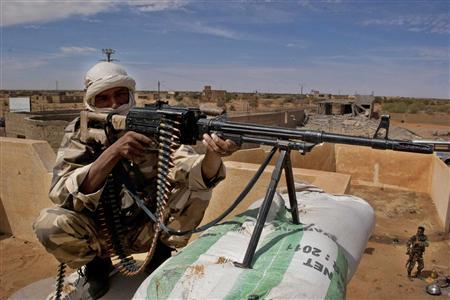 A Tuareg soldier in the Malian army aims his rifle at a checkpoint along a road leading to the border with Niger in the northern city of Gao, Mali February 9, 2013. REUTERS/Francois Rihouay