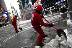 Workers clear snow at Times Square in New York, February 9, 2013. A blizzard pummeled the Northeastern United States, killing at least one person, leaving hundreds of thousands without power and disrupting thousands of flights, media and officials said. REUTERS/Eric Thayer