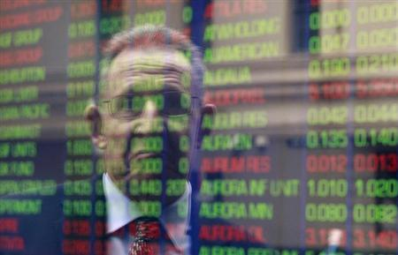 An office worker looks at the stock board at the Australian Securities Exchange (ASX) building in central Sydney June 15, 2012. REUTERS/Daniel Munoz/Files