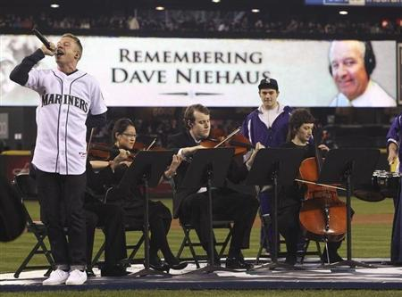 Rapper Macklemore (L) sings a song he wrote in memoriam of Seattle Mariners play-by-play commentator Dave Niehaus, who died in November 2010, during pre-game ceremonies honoring Niehaus before the Mariners' MLB home opener against the Cleveland Indians in Seattle April 8, 2011. REUTERS/Anthony Bolante/Files