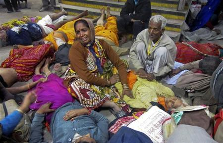 A woman cries as she sits among the bodies of people who were killed when part of a railing from a bridge collapsed at Allahabad railway station February 10, 2013. REUTERS/Stringer