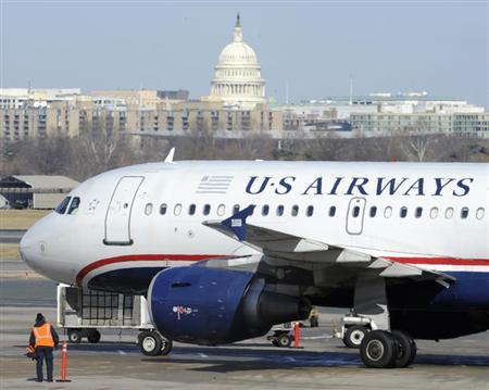 A US Airways plane arrives at the Ronald Reagan Washington National Airport in Arlington County, Virginia February 10, 2013, as negotiations continue this week between parent companies US Airways Group Inc and AMR Corp on a possible $11 billion merger, creating what would be the world's largest airline. The U.S. Capitol is seen in the background. REUTERS/Mike Theiler (UNITED STATES - Tags: TRANSPORT BUSINESS)