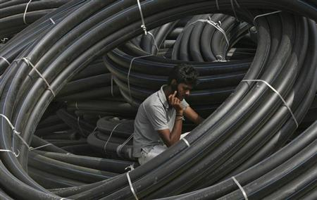 A construction supervisor speaks on a mobile phone amid rolls of underground telephone cable pipes on the outskirts of Hyderabad November 29, 2010. REUTERS/Krishnendu Halder