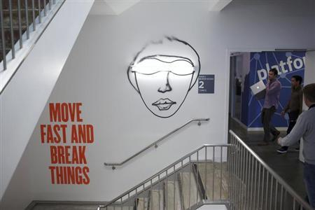 People walk past a graphic on a wall at the Facebook headquarters in Menlo Park, California January 29, 2013. REUTERS/Robert Galbraith