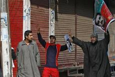 Activists from the Jammu Kashmir Liberation Front (JKLF), a Kashmiri separatist party, shout slogans as they hold posters of Mohammad Maqbool Bhat during a curfew in Srinagar February 11, 2013. About a dozen JKLF activists on Monday tried to hold a protest in the heart of Srinagar city to demand for the remains of Bhat. Bhat, founder and leader of JKLF, was hanged and buried in an Indian jail on February 11, 1984 on charges of killing an Indian intelligence officer. The activists were also protesting against the hanging of Mohammad Afzal Guru. India hanged Guru on Saturday for an attack on the country's parliament in 2001. Guru, from the Indian part of divided Kashmir, was convicted of helping organise arms for the gunmen who conducted the attack and a place for them to stay. He had denied any involvement in the conspiracy. REUTERS/Danish Ismail (INDIAN-ADMINISTERED KASHMIR - Tags: CIVIL UNREST CRIME LAW POLITICS)
