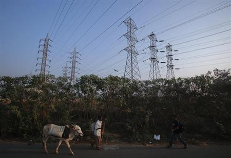 A man walks his cow under high-tension power lines leading from a Tata Power sub station in Mumbai's suburbs February 10, 2013. REUTERS/Vivek Prakash