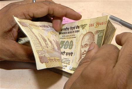 A cashier counts currency notes inside a bank in Lucknow July 16, 2009. REUTERS/Pawan Kumar/Files
