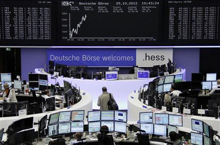 Traders are pictured at their desks in front of the DAX board at the Frankfurt stock exchange October 25, 2012. REUTERS/Remote/Marthe Kiessling