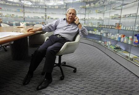 Y.K. Hamied, chairman and managing director of Cipla, speaks on his mobile phone in front of cabinets containing the company's products before an interview in Mumbai May 8, 2012. REUTERS/Vivek Prakash/Files