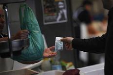Un cliente paga la merce al mercato dl pesce. REUTERS/Jon Nazca
