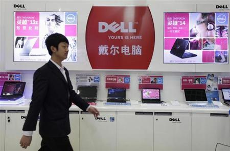 An employee walks past Dell laptops, which are displayed for sale, at a Dell outlet in Beijing December 13, 2010. REUTERS/Christina Hu/Files