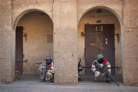 Malian soldiers crouch behind arched doorways during gun battles with Islamist insurgents in the northern city of Gao, Mali February 10, 2013. REUTERS/Francois Rihouay