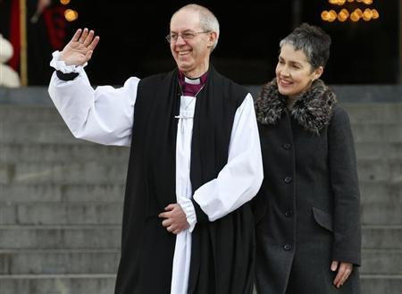 Justin Welby, the new Archbishop of Canterbury, waves as stands on the steps with his wife Caroline after a ceremony at St Paul's Cathedral in central London February 4, 2013. REUTERS/Andrew Winning