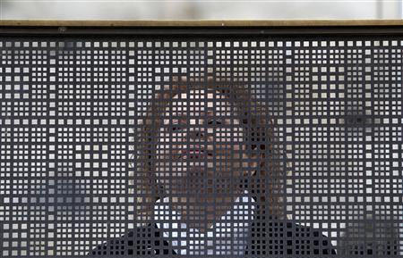 A woman stands behind a metal screen at the Western Wall in Jerusalem's Old City February 11, 2013. REUTERS/Baz Ratner