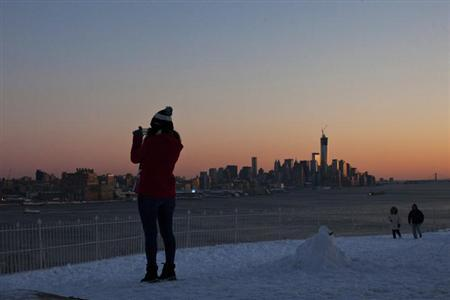 A woman take pictures of the skyline of New York and One World Trade Center from the side of Weehawken in New Jersey, February 9, 2013. REUTERS/Eduardo Munoz