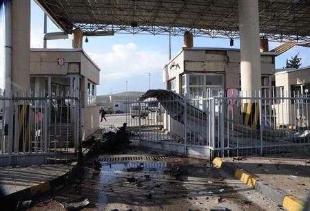 A man walks past a damaged gate after an explosion at Cilvegozu border gate on the Turkish-Syrian border in Hatay province February 11, 2013, in this picture taken by Anadolu Agency. A car exploded at the border crossing near the Turkish town of Reyhanli on Monday, killing at least seven people and wounding dozens more, officials said. REUTERS/Cem Genco/Anadolu Agency