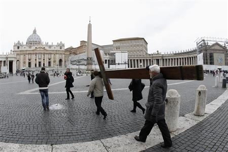 Pilgrims carry a cross as they arrive to pray in front of Saint Peter's Basilica at the Vatican February 11, 2013. REUTERS/Giampiero Sposito