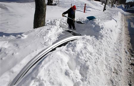 Julie MacDonald starts to dig her car out from snow in Somerville, Massachusetts February 10, 2013 following a winter blizzard which dumped up to 40 inches of snow with hurricane force winds, killing at least nine people and leaving hundreds of thousands without power. REUTERS/Brian Snyder