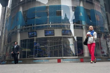 Commuters walk past the NASDAQ MarketSite in New York's Times Square May 22, 2012. REUTERS/Keith Bedford