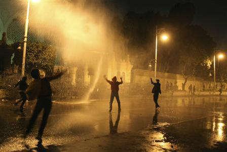 Protesters opposing Egyptian President Mohamed Mursi and the Muslim Brotherhood chant anti-government slogans while police spray water on them from inside the Presidential Palace, as some of the protesters try to break through one of the gates of the palace, in Cairo February 11, 2013. REUTERS/Asmaa Waguih (EGYPT - Tags: POLITICS CIVIL UNREST)