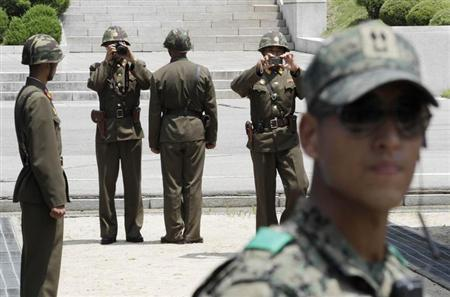 North Korean soldiers (background) take pictures, as a South Korean soldier (R) stands guard, after a ceremony marking the 59th anniversary of the signing of the armistice agreement that ended the Korean War on July 27, 1953, at the border villages of Panmunjom July 27, 2012. REUTERS/Ahn Young-joon/Pool/Files