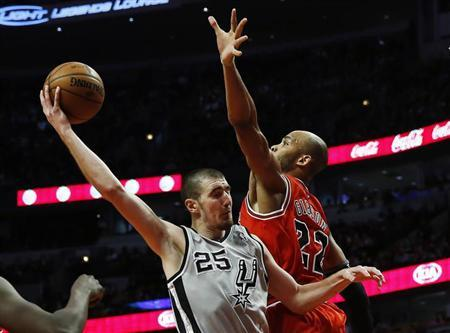 San Antonio Spurs' Nando de Colo (L) goes to the basket against Chicago Bulls' Taj Gibson during the second half of their NBA basketball game in Chicago, February 11, 2013. REUTERS/Jim Young