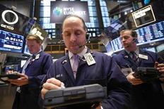 Трейдеры на Нью-Йоркской фондовой бирже 11 февраля 2013 года. Американские акции завершили торги понедельника с незначительными изменениями, так как инвесторы не нашли поводов для продолжения шестинедельного ралли. REUTERS/Brendan McDermid