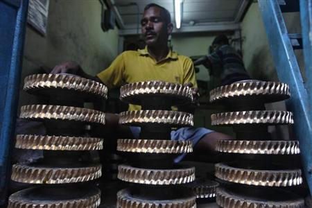 A worker cleans gear wheels used in conveyor belts at a small scale factory in Kolkata February 7, 2013. REUTERS/Rupak De Chowdhuri/Files