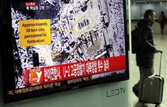 Пассажир проходит мимо телевизора, по которому идет репортаж про ядерные испытания в КНДР, на ж/д вокзале в Сеуле 12 февраля 2013 года. Северная Корея провела во вторник ядерные испытания, в очередной раз нарушив международные санкции к недовольству ООН, Запада и России. REUTERS/Kim Hong-Ji