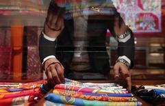 Продавщица раскладывает шарфы в магазине Hermes в Бомбее 23 августа 2011 года. Продажи французского производителя предметов роскоши Hermes поднялись на 16,4 процента в 2012 году, что оказалось выше собственного прогноза компании. REUTERS/Danish Siddiqui