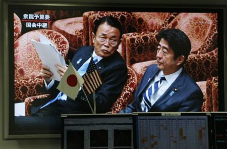 A television screen shows Japan's Prime Minister Shinzo Abe (R) and Finance Minister Taro Aso attending the lower house budget committee session at the parliament, behind a monitor showing information on currency exchange at a foreign exchange trading company in Tokyo February 12, 2013. The yen hovered near fresh lows against the dollar and Tokyo stocks jumped back near a 33-month high on Tuesday after markets took comments from a U.S. official as giving Japan the green light to pursue policies that weaken the yen as long as they help beat deflation. REUTERS/Toru Hanai (JAPAN - Tags: POLITICS BUSINESS)