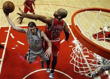 Los Spurs de San Antonio lograron el lunes una impresionante victoria por 103-89 frente a los Bulls de Chicago a pesar de no poder contar con sus tres mejores jugadores por lesión. En la imagen, de 11 de febrero, Nando de Colo de los Spurs en una jugada con Taj Gibson de los Bulls. REUTERS/Jim Young