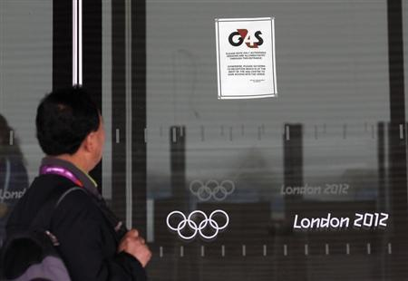 A visitor to the Olympic Park reads a G4S notice stuck to a window at the Aquatics centre, in the Olympic Park, in Stratford, east London, July 17, 2012. REUTERS/Andrew Winning
