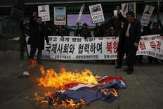 "Activists from an anti-North Korea civic group burn a North Korea flag in front of banners bearing anti-North Korea messages near the U.S. embassy in central Seoul February 12, 2013. North Korea conducted its third-ever nuclear test on Tuesday, a move likely to anger its main ally China and increase international action against Pyongyang and its new young leader, Kim Jong-un. U.N. Secretary-General Ban Ki-moon condemned North Korea's test, saying it was a ""clear and grave violation"" of U.N. Security Council resolutions. The banner in the background reads, ""Cease nuclear test and cooperate with the international powers!"" REUTERS/Kim Hong-Ji (SOUTH KOREA - Tags: CIVIL UNREST POLITICS TPX IMAGES OF THE DAY)"