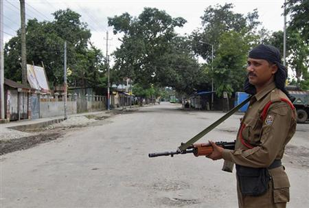 A security personnel stands guard on a deserted street during a curfew at Kokrajhar town in Assam July 24, 2012. REUTERS/Stringer