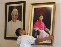 A worker hangs a portrait of Cardinal Luis Antonio Tagle of the Philippines (R) next to a portrait of Pope Benedict XVI inside the Roman Catholic Archbishop headquarters in Manila February 12, 2013. REUTERS/Romeo Ranoco
