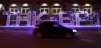 Автомобиль проезжает мимо подсвеченного логотипа ТНК-ВР возле офиса компании в Тюмени 17 января 2013 года. Роснефть во вторник подпишет соглашение о синдицированном кредите на $13 миллиардов на покупку ТНК-ВР, сообщили близкие к сделке источники. REUTERS/Eduard Korniyenko