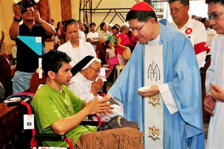 Cardinal Luis Antonio Tagle anoints the sick with holy oil during a mass for World Day of the Sick at the Espiritu Santo Church in Manila, February 11, 2013. REUTERS/Noli Yamsuan/Archbishop Palace/Handout