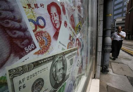 Photos of yuan (top) and U.S. dollar banknotes are displayed at a money exchange in Hong Kong September 13, 2010. REUTERS/Bobby Yip/Files