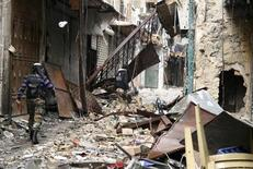 Members of the Free Syrian Army walk through rubble and damaged buildings near the Umayyad Mosque in Aleppo February 11, 2013.
