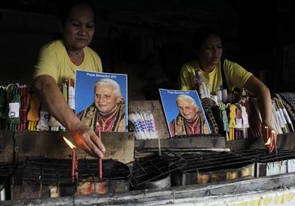 Residents display pictures of Pope Benedict at a shop selling church candles outside a Roman Catholic church in Antipolo, Metro Manila, February 12, 2013. REUTERS/Erik De Castro