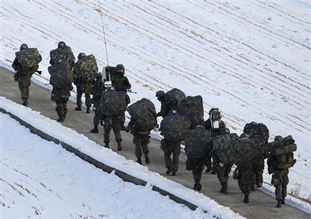 A South Korean soldier (C) looks back as his colleague soldiers march during a military drills near the demilitarized zone separating North Korea from South Korea, in Paju, north of Seoul February 12, 2013. North Korea conducted its third nuclear test on Tuesday in defiance of U.N. resolutions, angering the United States and Japan and prompting its only major ally, China, to call for calm. REUTERS/Lee Jae-Won (SOUTH KOREA - Tags: MILITARY POLITICS) - RTR3DO9W
