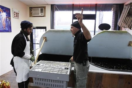 Small-business owner Ralph Gorham (R) speaks to employee Elijah Ocean at his shop ''Redhook Lobster Pound'' in New York December 16, 2010. REUTERS/Lucas Jackson