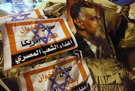 A protester opposing Egyptian President Mohamed Mursi walks outside tents near a picture of Egypt's former president Gamal Abdel Nasser during a sit-in at Tahrir Square in Cairo in this January 31, 2013 file photo. In Egypt, Libya and Syria, where Qatar tried to play a role post-Arab Spring, it finds itself blamed for much that has gone wrong on a local level. Close ties to Egypt's new leaders, the Muslim Brotherhood, have alarmed countries like the United Arab Emirates, where the Islamist group is still banned and which in January said it had foiled a Brotherhood-linked coup plot. The Arabic words printed over the Star of David read, ''Qatar, U.S., Hamas and the Brotherhood are the enemies of Egypt''. REUTERS/Amr Abdallah Dalsh/Files