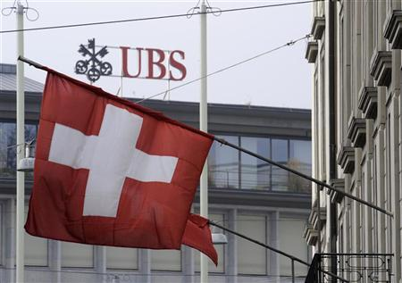 A Swiss flag is seen in front of an UBS logo on Swiss bank UBS headquarters in Zurich in this November 15, 2008 file photo. REUTERS/Christian Hartmann/Files