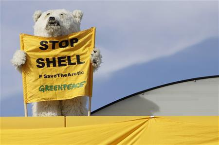 A Greenpeace environmental activist in a polar bear costume holds up a banner at a Shell gas station in Prague in this May 10, 2012 file photo. REUTERS-David W Cerny-Files