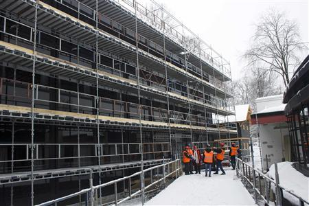 Workers stand at the entrance to an office block in Sandvika February 4, 2013. Two office blocks by the Oslo fjord will generate more power than they use from 2014 after a radical refit meant to show that the world's energy-squandering building sector can do more to fight climate change. REUTERS/Alister Doyle