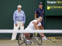 Esther Vergeer of the Netherlands serves, with her partner Sharon Walraven of the Netherlands (UNSEEN), to Marjolein Buis of the Netherlands and Annick Sevenans of Belgium, during their wheelchair doubles match at the Wimbledon tennis championships in London July 1, 2011. REUTERS/Eddie Keogh